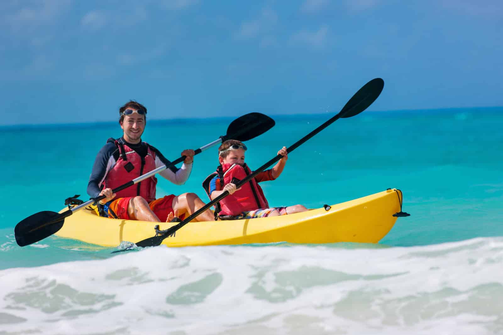 father and son kayaking on ocean